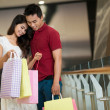 Asian man and woman standing and looking in a shopping bag — Stock Photo #19986655