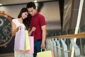 Asiático hombre y mujer de pie y mirando en una bolsa de compras — Foto de Stock