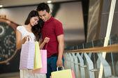 Asiático homem e mulher em pé e olhando numa sacola de compras — Foto Stock