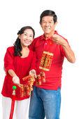Grandparents holding Tet decorations — Stock Photo