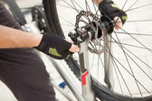 Cyclist repairing the wheel of his bicycle — Stock Photo