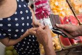 Adam tutarak para meyveler için — Stok fotoğraf