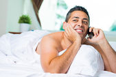 Man in bed and phone — Stock Photo