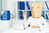 Businesswoman with paperbag on head — Stock Photo