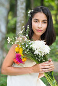 Brunette holding bouquet of flowers — Stock Photo