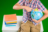 Schoolboy pointing at the globe — Stock Photo