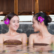 Two Asian girls relaxing in bath in spa — Stock Photo
