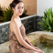 Woman sitting on the poolside in spa — Stock Photo