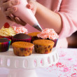 Hands decorating cupcakes — Stock Photo