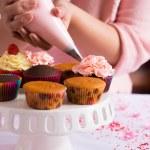 Hands decorating cupcakes — Stock Photo #50358505