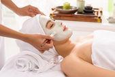 Young woman receiving white facial mask — Stock Photo