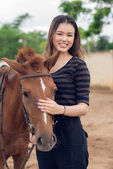 Girl stroking brown pony — Photo