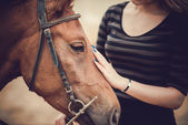 Horsewoman stroking her pet — Stock Photo
