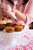 Hands decorating cupcakes — Stockfoto