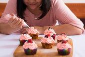 Woman enjoying cooking cupcakes — Stock Photo