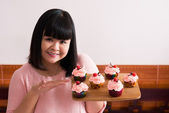 Baker holding tray with cupcakes — Stock Photo