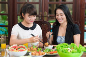 Mother and daughter dipping meat pieces — Stock Photo