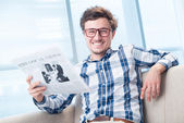 Cheerful man reading daily newspaper — Stock Photo