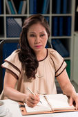 Pensive business woman writing — Stock Photo