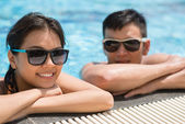 Woman and her boyfriend relaxing in pool — Stock Photo