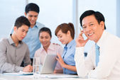Businessman and his busy employees — Stock Photo