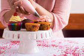 Girl decorating cupcakes — 图库照片