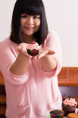 Young Asian showing a cupcake — Stock Photo
