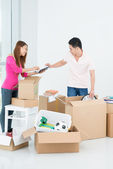Asian family unpacking in new apartment — Stock Photo