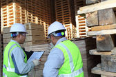 Two workers talking beside on stacking pallet — Stock Photo