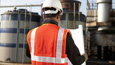 Engineer on location site with blueprint — Stock Photo