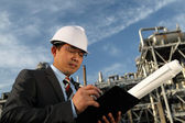 Businessman with oil refinery background — Stockfoto