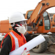 Stock Photo: Construction worker with building plans and cellphone
