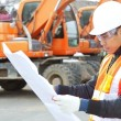 Stock Photo: Road construction worker with heavy equipment on the background