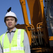 Portrait construction worker standing front of heavy equipment - Stock Photo