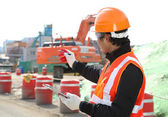 Road construction worker in front of excavator — Stock Photo
