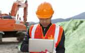 Road construction worker using laptop — Stock Photo