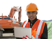 Construction worker and excavator — Stock Photo