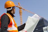Construction worker with crane in background — Stock Photo