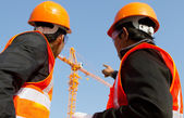 Site manager with safety vest discussion under construction — 图库照片