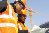 Construction workers with crane in background — Stock Photo