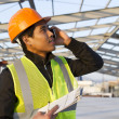 Engineer construction talking mobile phone under new building - Stock Photo