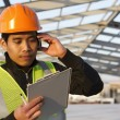 Engineer construction talking mobile phone under new building — Stock Photo #24486243