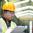 Factory worker writing on clipboard — Stock Photo