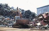 Ndustrial heap of metal and excavator — Stock Photo