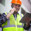 Portrait of construction worker wearing safety vest talking on t — Stock Photo