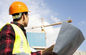 Builder with blueprint at construction site — Stock Photo