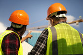 Construction worker pointing yellow crane — Stock Photo