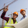 Young asian architects discussion front of construction site — Stock Photo #30915455
