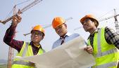 Grupp asiatiska arkitekt diskussion framsidan av ett bygge — Stockfoto