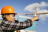 Construction worker and crane on the background talking via mobi — Stock Photo